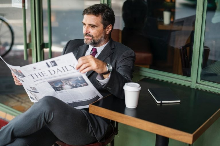 man in suit reading newspaper