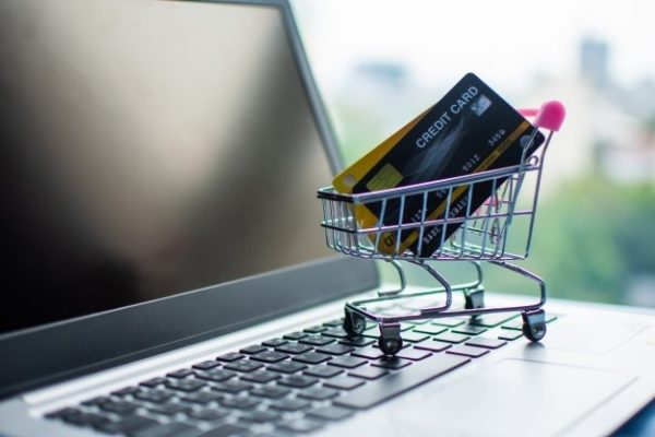 credit cards in minature shopping trolley on laptop